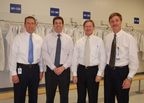 (L to R) John Kania, Government Affairs, Applied Materials, Mike Dabbs, Government Affairs, Applied Materials, Congressman Smith and Rick Gesing prepare for a tour of Applied's Austin facility.